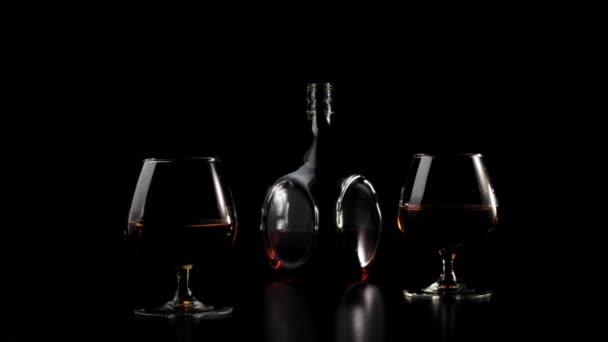 Luxusbrandy. Arany konyak kerek üvegben áll közel két pohár egy fekete asztal fekete háttér. Fénysugár ragyog az asztalon, üveg vakít a fényben. Alkohol a szipogóban. 4k.