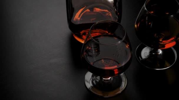 Luxusbrandy. Kerek üveg arany konyakkal és két pohár forog a fekete asztal fekete háttér. Üvegcsillogás a fényben. Brandy, konyak, snifter, binge. Lassú mozgás. 4k.