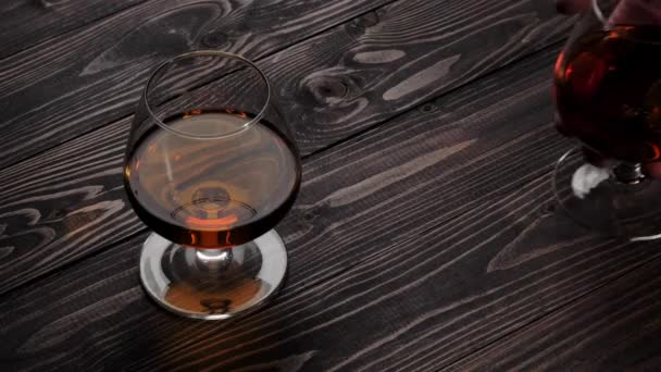 Luxury brandy. Hand puts one of two glasses with golden cognac on wooden table. Brandy, cognac, snifter, binge. Slow motion. 4K.
