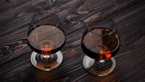 Luxusbrandy. Kézzel vesz egyet a két pohár arany konyakkal fa asztalról. Brandy, konyak, snifter, binge. Lassú mozgás. 4k.