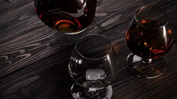 Luxusbrandy. A kéz fogja a kerek üveget, és arany konyakot tölt a két pohár egyikébe a fa asztalon. Brandy, konyak, snifter, binge. Lassú mozgás. 4k.