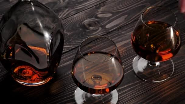 Luxusbrandy. A kéz a két pohár egyikét veszi le a jobb oldalról a fa asztalról. Brandy, konyak, snifter, binge. Lassú mozgás. 4k.