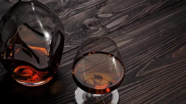 Luxusbrandy. A kéz a jobb oldali két pohár egyikét rakja a fa asztalra. Brandy, konyak, snifter, binge. Lassú mozgás. 4k.