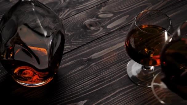 Luxusbrandy. A kéz a bal oldali két pohár egyikét rakja a fa asztalra. Brandy, konyak, snifter, binge. Lassú mozgás. 4k.