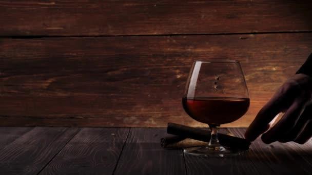 Luxusbrandy. Egy pohár arany konyak van az asztalon. Kéz vesz egy barna szivar egy fa asztal egy fa háttér. Brandy, konyak, snifter, binge. Lassú mozgás. 4k.