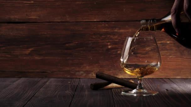 Luxusschnaps. Zwei Zigarren stehen auf dem Tisch. Hand gießt Goldcognac aus einer runden Flasche in Glas auf einem Holztisch vor Holzgrund. Schnaps, Cognac, Schnüffler, Saufgelage, Zigarre. Zeitlupe. 4k.