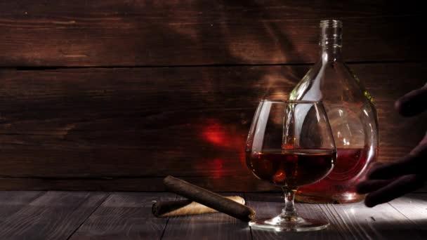 Luxusbrandy. Kerek üveg és üveg arany konyakkal az asztalon. Kézzel vesz egy üveg arany konyak fa asztalról fából készült háttér. Brandy, konyak, snifter, binge, szivar. Lassú mozgás. 4k.