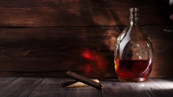 Luxusbrandy. Kerek üveg és két szivar van az asztalon. Kéz tesz egy üveg arany konyakkal a fa asztalra, fa háttér. Brandy, konyak, snifter, binge, szivar. Lassú mozgás. 4k.
