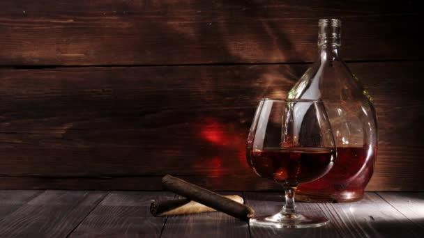 Luxusbrandy. Kerek palack, üveg arany konyakkal és két szivar van az asztalon fa háttér. Brandy, konyak, snifter, binge, szivar. Lassú mozgás. 4k.
