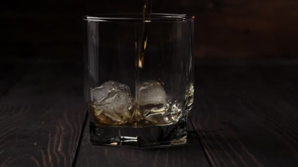 Luxus whisky. A kéz arany whiskyt önt egy négyzet alakú üvegből egy pohárba, hideg jéggel az asztalon, fa háttér mellett. Whisky szósszal. Bourbon whiskyben. Lassú mozgás. Közelről..
