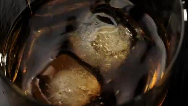 Luxus whisky. Jégkockák esnek egy pohár whisky fröccsenő található egy fekete asztalon a fa háttér. Whisky szósszal. Bourbon whiskyben. Lassú mozgás. Közelről..