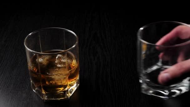 Luxus whisky. A kéz üres üveget helyez az üveg mellé arany whiskyvel, hideg jéggel a fekete asztalon. Whisky szósszal. Bourbon whiskyben. Lassú mozgás..