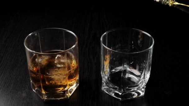 Luxus whisky. A kéz arany whiskyt önt egy négyzet alakú üvegből egy pohárba a fekete asztalon üveg mellett whiskyvel és jéggel. Whisky szósszal. Bourbon magas labdában.