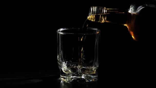 Luxusní whisky. Ruka nalévá zlatou whisky ze čtvercové láhve do sklenice na točícím se černém stole. Skotskou s pohárem. Bourbon ve whisky. Zpomal. Zavřít.