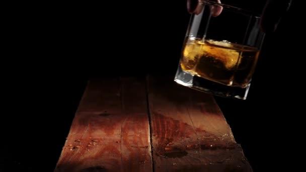 Luxus whisky. A kéz egy pohár arany whiskyt tesz jégkockákkal a barna fa asztalra. Alkoholfogyasztásra való felkészülés. Whisky szósszal. Bourbon whiskyben. Lassú mozgás..