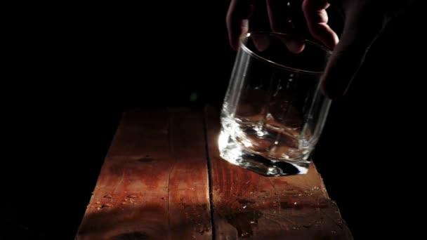 Luxus whisky. Kéz tesz egy üres poharat a barna fa asztal fekete háttér. Alkoholfogyasztásra való felkészülés. Whisky szósszal. Bourbon whiskyben. Lassú mozgás..