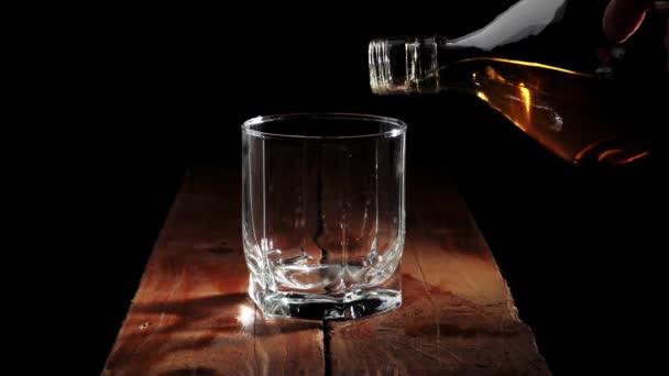 Luxus whisky. A kéz arany whiskyt önt egy négyzet alakú üvegből egy pohárba a barna fa asztalra, fekete háttér mellett. Whisky szósszal. Bourbon whiskyben. Lassú mozgás..