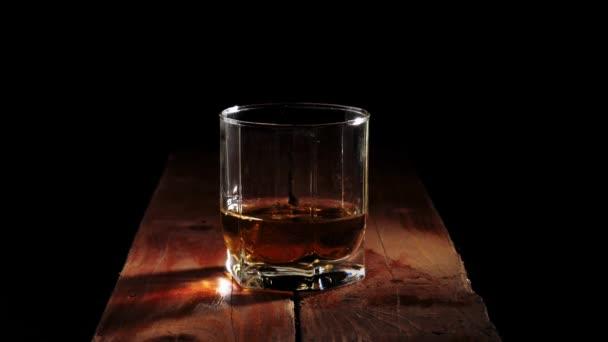 Luxus whisky. Jégkockák hullanak a fröccsenő egy pohár arany whisky a barna fa asztal fekete háttér. Whisky szósszal. Bourbon whiskyben. Lassú mozgás..