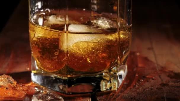 Luxus whisky. A jég lebeg és forog egy pohár arany whiskyben a barna fa asztalon. Whisky szósszal. Bourbon whiskyben. Lassú mozgás. Közelről..