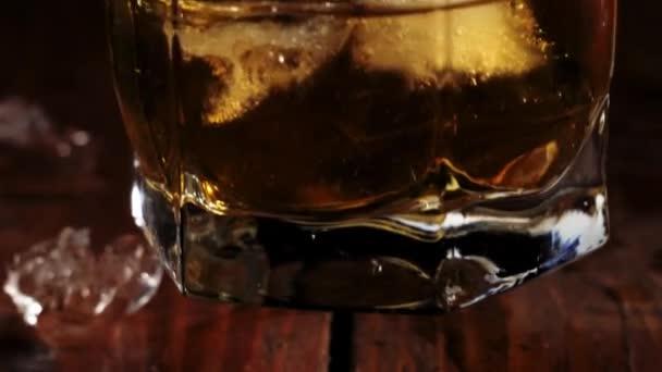 Luxus whisky. A kéz vesz egy pohár arany whiskyt jégkockákkal a barna fa asztalról. Alkoholfogyasztásra való felkészülés. Whisky szósszal. Bourbon whiskyben. Lassú mozgás..