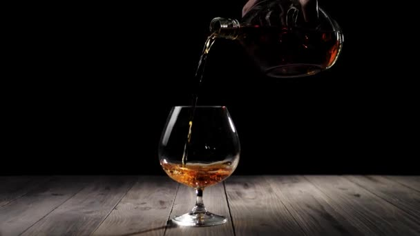 Luxury brandy. Hand pours gold cognac from a round bottle into a glass on wooden table against black background. Brandy, cognac, snifter, binge. Slow motion.