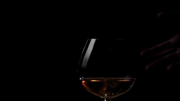 Luxusbrandy. Kézzel vesz egy pohár arany konyak fa asztalról fekete háttér. Brandy, konyak, snifter, binge. Lassú mozgás. Közelről..