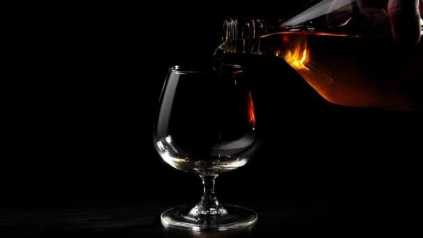 Luxusbrandy. A kéz arany konyakot önt egy kerek üvegből egy pohárba forgó fekete asztalon fekete háttér mellett. Brandy, konyak, snifter, binge. Lassú mozgás..