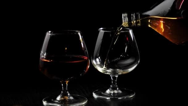 Luxusbrandy. Kézzel töltött arany konyakot egy kerek üveg egy pohár forgó fekete asztal mellett üveg konyakkal fekete háttér. Brandy, konyak, snifter, binge. Lassú mozgás..