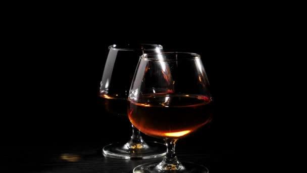 Luxusbrandy. Két konyakos pohár forog egy fekete asztalon fekete háttér mellett. Brandy, konyak, snifter, binge. Lassú mozgás..
