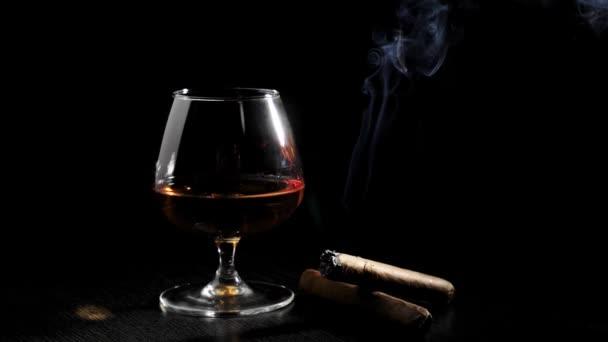 Luxusbrandy. Üveg konyakkal, két szivar és füst szivar forog egy fekete asztalon fekete háttér. Brandy, konyak, snifter, binge. Lassú mozgás..