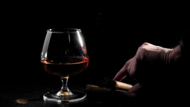 Luxusbrandy. Üveg konyakkal és két szivar forog egy fekete asztalon fekete háttérrel. A kéz vesz egy szivart. Brandy, konyak, snifter, binge. Lassú mozgás..