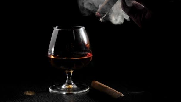 Luxusbrandy. Üveg konyakkal és szivarral egy fekete asztalon fekete háttérrel. Egy szivarozó férfi. Brandy, konyak, snifter, binge. Lassú mozgás..