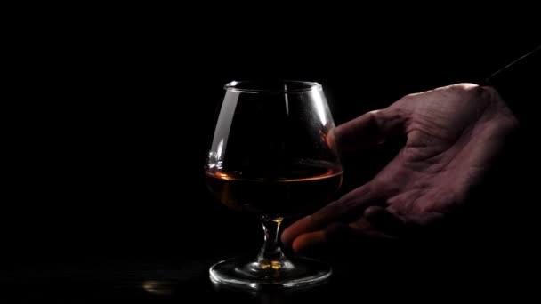 Luxusbrandy. Üveg arany konyakkal a fekete asztalon fekete háttérrel. A kéznek kell egy pohár ital. Brandy, konyak, snifter, binge. Lassú mozgás..