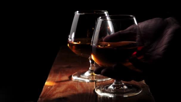 Luxusbrandy. Két pohár arany konyak barna fa asztal fekete háttér. A kéznek jobb pohár kell az iváshoz. Brandy, konyak, snifter, binge. Lassú mozgás..