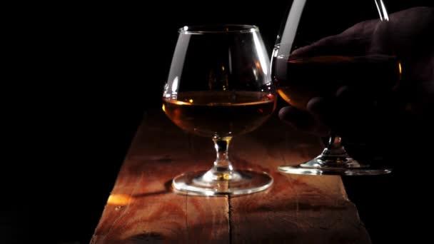 Luxusbrandy. Üveg arany konyakkal barna fa asztalon fekete háttér. A kéz tesz még egy poharat konyakkal az asztalra. Brandy, konyak, snifter, binge. Lassú mozgás..