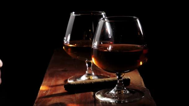 Luxusbrandy. Két pohár arany konyakkal és szivarral barna fa asztalon fekete háttérrel. A kéznek kell egy szivar, hogy rágyújtson. Brandy, konyak, snifter, binge. Lassú mozgás..