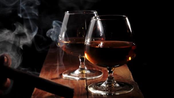 Luxusbrandy. Két pohár arany konyak barna fa asztal fekete háttér. Egy szivarozó férfi. A füst felszáll. Brandy, konyak, snifter, binge. Lassú mozgás..