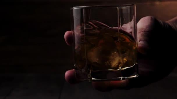 Luxusní whisky. Muž míchat pomalu zlatou whisky ve sklenici s ledem na dřevěném pozadí. Skotskou s pohárem. Bourbon ve whisky. Zpomal. Zavřít.