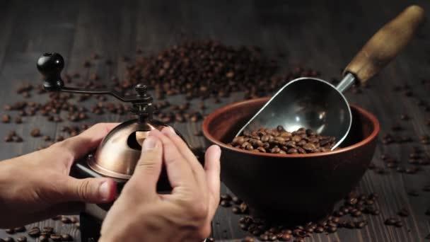 Složení z kávových zrn. Dřevěné stolní pozadí zdobené taškou s kávovými zrny, miskou a lopatkou s voňavými kávovými zrny. Ruka zavře mlýnek na kávu. 4k