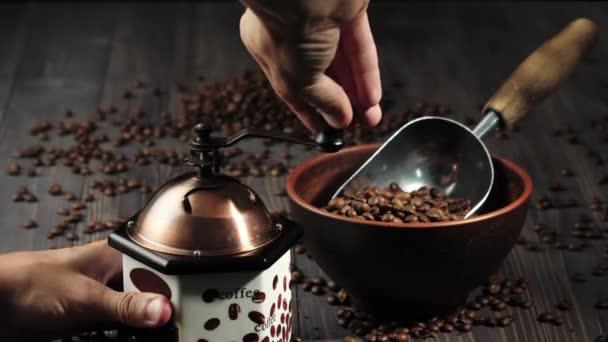 Složení z kávových zrn. Dřevěné stolní pozadí zdobené taškou s kávovými zrny, miskou a lopatkou s voňavými kávovými zrny. Ručně mele kávu v mlýnku. 4k