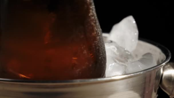 Frisches Bier. eine braune Flasche mit leckerem Craft Beer rotiert mit einem Eimer mit kaltem Echteis vor schwarzem Hintergrund. kaltes frisches Bier mit Wassertropfen. bereit zum Trinken. Nahaufnahme. 4k.