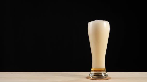 Čerstvé pivo. Lahodné řemeslné pivo ve skle na horské dráze do dřevěného stolu na černém pozadí. Studené čerstvé pivo s kapkami vody, bublinkami a pěnou. Připraven k pití. 4k