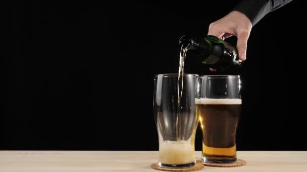 Friss sör. Kézzel töltött egy finom kézműves sört a második pohár sör alátét barna palack egy fa asztal fekete háttér. Hideg, friss sör vízcseppekkel, buborékokkal és habbal. 4k