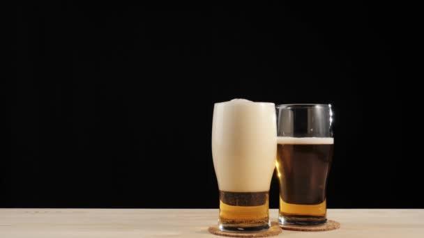 Friss sör. Finom kézműves sör üveg sör alátét mellett más üveg egy fa asztal fekete háttér. Hideg, friss sör vízcseppekkel, buborékokkal és habbal. 4k