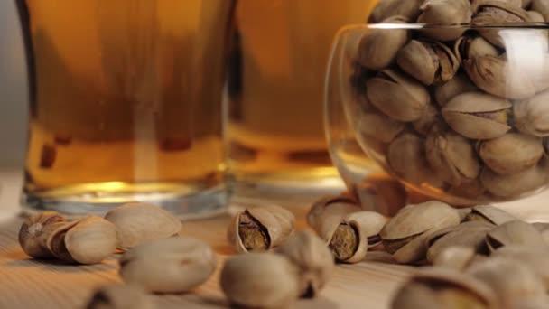 Friss sör. Két pohár finom hideg sör mellett csészealj néhány pisztácia egy fa asztal fehér háttér. Hideg, friss sör vízcseppekkel, buborékokkal és habbal. Közelről. 4k