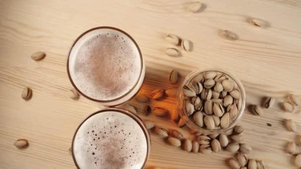 Čerstvé pivo. Dvě sklenice s lahodným studeným pivem u talíře s pistáciemi do dřevěného stolku na pozadí. Studené čerstvé pivo s kapkami vody, bublinkami a pěnou. Horní pohled. 4k