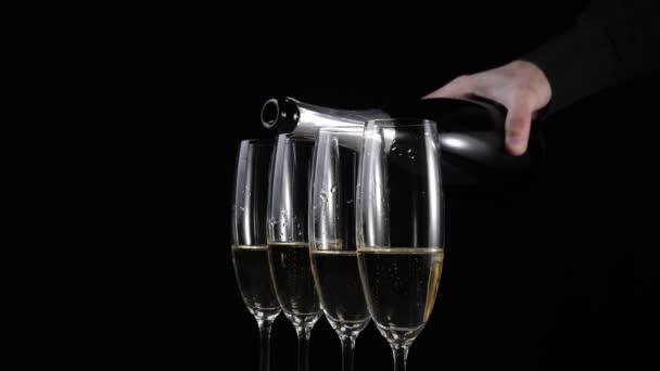 Süßer Champagner. Auf einem Holztisch vor schwarzem Hintergrund stehen vier Sektgläser. Hand gießt Goldchampagner in die ersten beiden Gläser. Flöten mit Sekt. Neujahrsparty. 4k