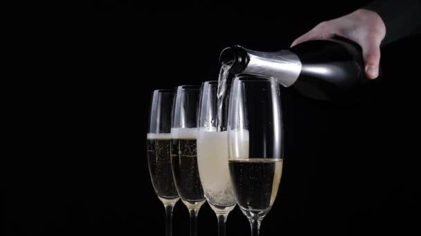 Édes pezsgő. Négy pohár pezsgővel áll egy fa asztalon fekete háttér mellett. A kéz arany pezsgőt önt a második két pohárba. Furulyák pezsgővel. Újévi buli. 4k