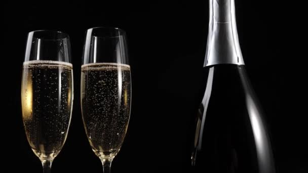Sladké šampaňské. Dvě sklenice se šampaňským a láhev se šampaňským stojí na dřevěném stole na černém pozadí. Flétny se šumivým vínem. Nový rok. Oslava. 4k