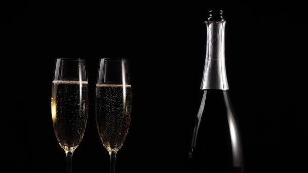 Sladké šampaňské. Ruka vezme sklenici se zlatým šampaňským z dřevěného stolu na černém pozadí. Flétny se šumivým vínem. Novoroční párty. Oslava. 4k